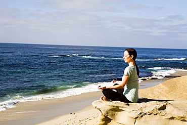A women meditates on the beach.