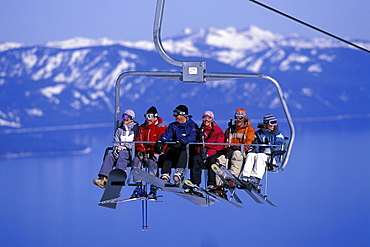 Ski and snowboard buddies enjoy their chairlift ride high above blue Lake Tahoe while skiing at Heavenly Mountain Resort in South Lake Tahoe, California.
