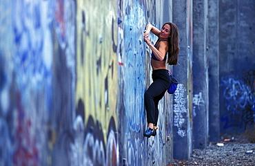 Sabina Allemann buildering on a graffiti covered wall in San Jose, California.