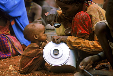 Malnourished mother and child share a little food at distribution in Baidoa, Somalia.