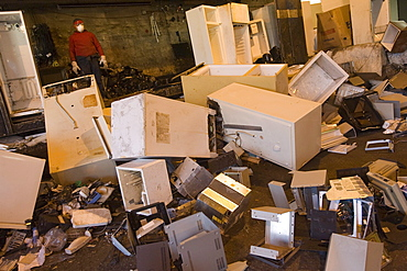 At CRT Recycling in Brockton, Massachusetts a worker recycles old refrigerators for electronic components and copper.