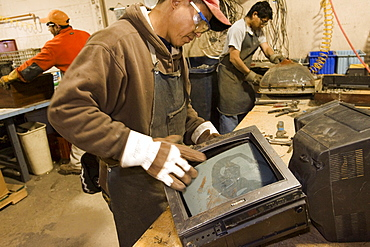 Workers at ElectroniCycle, a recycling company in Gardner, Massachusetts take apart old televisions for recycling.