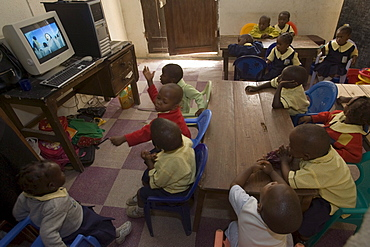 """Yinka Ogunsuyi teaches a computer class to 9-11 year olds from the Regency School in Lagos, Nigeria. He gets the computers from a contact in the USA and also buys some in Nigeria. The computer is a Pentium 3 Dell from the USA. Also at the school 2-3 year olds watch the movie """"Happy Feat"""" on a Pentium 4 computer."""