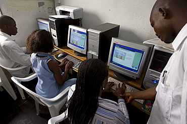 A computer training institute in Lagos, Nigeria. The Pentium 2 computers were bought second hand in Nigeria and there are about 16 computers at this location. Students are learning various software programs including typing, Microsoft word and a drawing program. One student in the striped shirt is Alice Itodo.