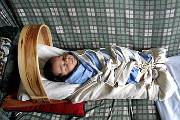 Stephan Begay, five week old Native American Indian baby naps swaddled on a backboard at home on the Navajo Reservation in Northeastern Arizona on March 22, 2007. The baby's mother is Hopi and the father is Navajo, so the baby is part of two tribes. There is a small Hopi Reservation in Kykotsmovi Arizona that is located within the very large Navajo reservation in the northeastern corner of the state, yet intermarriage is rare. Babies are kept on traditional  backboards until they start to crawl.