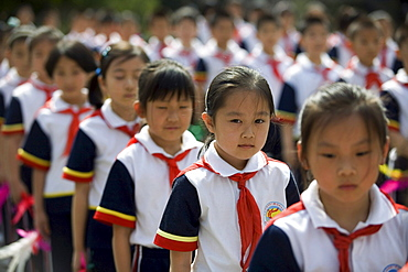 Chinese seven-year-old Shen Siyue stands surrounded by classmates as they line up for morning exercises at her elite school at in Beijing, China.