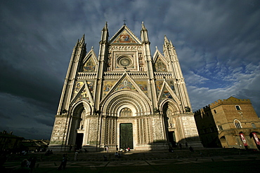 Orvieto, Umbria, Italy, during a late spring sunset.  Orvieto is noted for its Gothic cathedral, or duomo. The church is striped in white travertine and greenish-black basalt in narrow bands; its design has often been attributed to Arnolfo di Cambio, but the prevailing modern opinion is that its master mason was an obscure monk named Fra' Bevignate from Perugia; construction began in 1290.