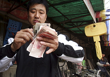"""A man counts """"Ren Min Bi"""", China's currency, which translates in to """"The People's Money"""" in Songzhuang Village, in Beijing's eastern suburbs."""