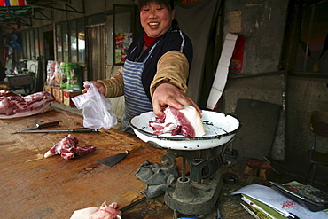 A woman sells a fatty cut of pork in a market in Songzhuang Village, in Beijing's eastern suburbs, China.