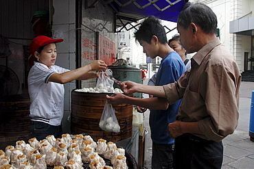 Customers queue up to buy dim-sum style snack foods at a street corner food kitchen near Beijing Dong Lu, central Shanghai, China. In the foreground are shu mei - thin skinned, filled with rice and usually diced pork.