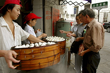 Customers queue up to buy dim-sum style snack foods at a street corner food kitchen near Beijing Dong Lu, central Shanghai, China.