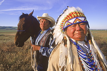 Chief of the Umatilla Tribes, Raymond Burke, Wish low tu latin, wears a traditional feather bonnet.