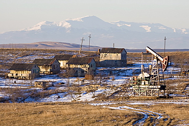 Tbilisi, Georgia - January, 2008: Village outside Tbilisi with an oil pump and mountains in the background.  Georgia has very limited supplies of its own oil compared to its neighbor Azerbaijan.