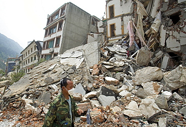 A man walks past a collapsed building in Beichuan Town, which was severely damaged by a powerful 7.9 earthquake. The Chinese government raised the death toll to 21,500 but has said fatalities could rise above 50,000. Tens of thousands could still be buried in collapsed buildings in Sichuan province, where the quake was centered.