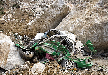 A small vehicle is smashed beyond recognition after being hit by large bounders in Beichuan Town, which was severely damaged by a powerful 7.9 earthquake. The Chinese government raised the death toll to 21,500 but has said fatalities could rise above 50,000. Tens of thousands could still be buried in collapsed buildings in Sichuan province, where the quake was centered.
