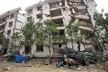 A mangles car is seen in front of a partially collapsed building in Beichuan Town, which was severely damaged by a powerful 7.9 earthquake. The Chinese government raised the death toll to 21,500 but has said fatalities could rise above 50,000. Tens of thousands could still be buried in collapsed buildings in Sichuan province, where the quake was centered.