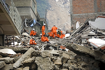 A rescue team look for survivors in the rubble of Beichuan Town, which was severely damaged by a powerful 7.9 earthquake. The Chinese government raised the death toll to 21,500 but has said fatalities could rise above 50,000. Tens of thousands could still be buried in collapsed buildings in Sichuan province, where the quake was centered.