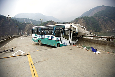A bus is seen on a road wrecked by Monday's powerful earthquake.  The Chinese government raised the death toll to 21,500 but has said fatalities could rise above 50,000. Tens of thousands could still be buried in collapsed buildings in Sichuan province, where the quake was centered.