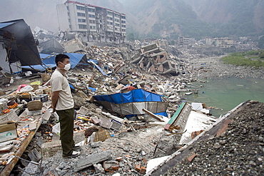 A man look out at Beichuan Town, which was severely damaged by a powerful 7.9 earthquake. The Chinese government raised the death toll to 21,500 but has said fatalities could rise above 50,000. Tens of thousands could still be buried in collapsed buildings in Sichuan province, where the quake was centered.