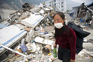 A woman walks through the rubble of Beichuan Town, which was severely damaged by a powerful 7.9 earthquake. The Chinese government raised the death toll to 21,500 but has said fatalities could rise above 50,000. Tens of thousands could still be buried in collapsed buildings in Sichuan province, where the quake was centered.
