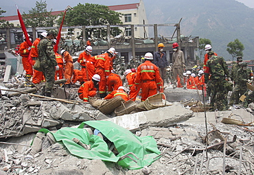 A green plastic sheet covers bodies at the scene of destruction at a middle school in Beichuan Town. The Chinese government raised the death toll to 21,500 but has said fatalities could rise above 50,000. Tens of thousands could still be buried in collapsed buildings in Sichuan province, where the quake was centered,
