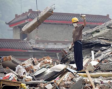 A rescue worker directs a crane where to move a large chunk of concrete from a building that collapsed during a powerful earthquake in Hongbai Vilage, China.