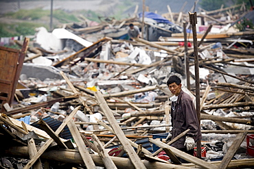 A man rifles through the debris of what was his home, destroyed by an earthquake in Yinghua Village, China.