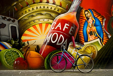 Bicycle sits next to painted wall in downtown Den Haag, The Netherlands.