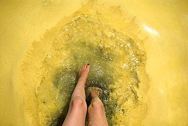 Feet dip in pollen covered lake water, Sebago Lake, Maine.