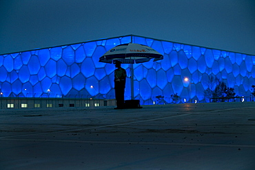 CHINA/Beijing/National Aquatic Center/17June2008:A soldier stands guard outside the National Aquatic Center at night. Designed by Australia's PTW Architects, its facade appearing as a cube of soap bubbles, it seats 17,000 people. The exterior is made from a high-tech lightweight translucent plastic that is also very energy efficient in saving an estimated 30% in power consumption by comparison to a traditional design. It houses 5 pools - one able to create it's own waves. It's outer surface looks like soap bubbles. It will host all swimming and diving events at the 2008 Olympics.