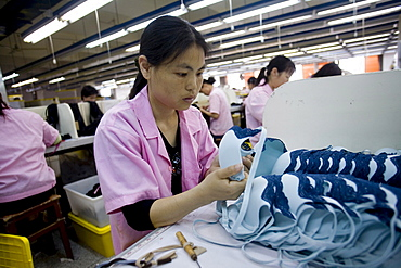A woman inspects the quality of a batch of blue bras in the Top Form factory in Longnan, China.