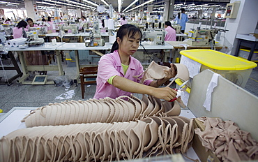 A woman inspects the quality of a batch of flesh colored bras in the Top Form factory in Longnan, China.