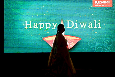 """A silhouette of a woman walking in front of an electronic billboard wishing a happy Diwali to passerby's in Mumbai, India. Diwali is a major Hindu holiday and is known as the """"Festival of Lights"""".  The five day festival occurs during October and/or November."""