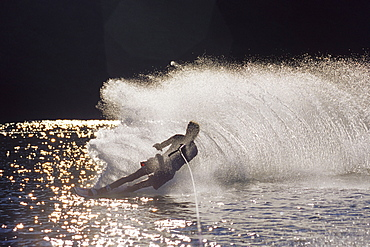 Male water skier backlit by the sun.