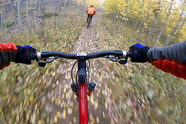 The view over the handlebars of a moving mountain bike.
