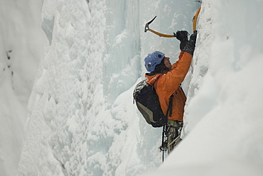 A young man ice climbing a frozen waterfall with a backpack in Colorado.