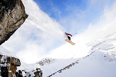 A male skier jumps off a cliff while skiing in the Wyoming back country.