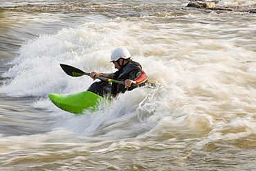 A male whitewater kayaker front surfs his boat.