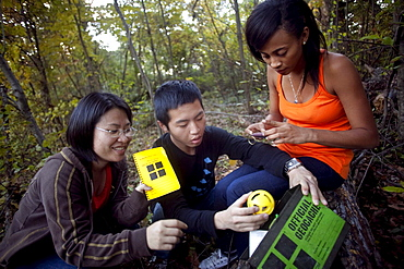 Three friends find a geocache in a park in Baltimore, Maryland.