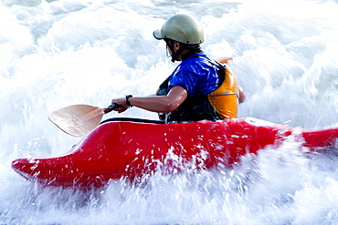 A female kayaker in a playboat battles the rapids of Brennan's Wave on the Clark Fork River, Missoula, Montana.