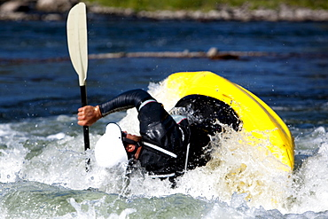 A male kayaker flips in a playboat rides the rapids of Brennan's Wave, Missoula, Montana.