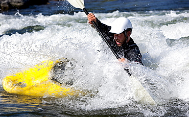 A male kayaker in a playboat battles the rapids of Brennan's Wave, Missoula, Montana.