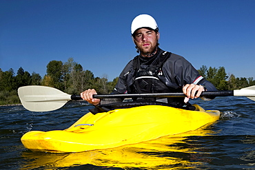 A male kayaker in a yellow playboat looks into the camera on the Clark Fork River, Missoula, Montana.