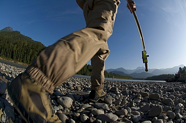 A man holding a fishing rod walks to the river to go fly fishing in Squamish, Brithish Columbia. (motion blur)