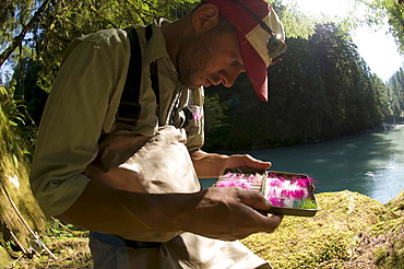 A man picks a fly from his fly box while  fishing in Squamish, British Columbia.