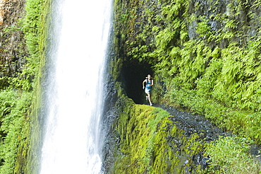 A woman running along trail blasted into a hill behind a waterfall on the Pacific Crest Trail, Oregon.