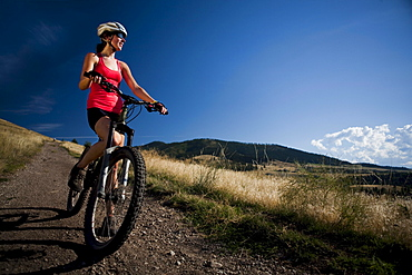 A female mountain biker stops to enjoy the view while riding the trails of Mt. Sentinel, Missoula, Montana.