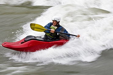 A young man surfing a wave in a whitewater kayak, Elk river, East Kootenies, British Columbia, Canada.