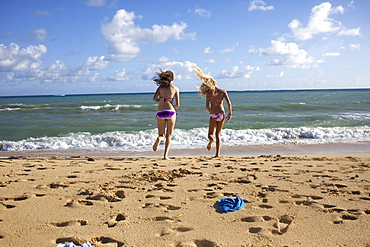 Two pre-teen girls undressing as they run into the water at Paia Beach, Maui, Hawaii.