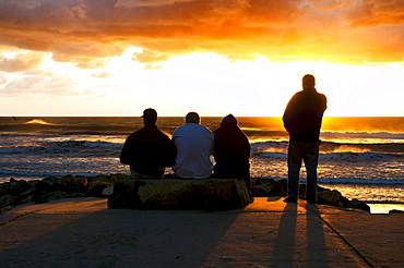 Four men watching the sunset on the ocean on a stormy day in San Diego, California.